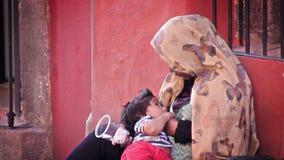 Μια γυναίκα θηλάζει το μωρό της ικετεύοντας στην οδό απόθεμα βίντεο