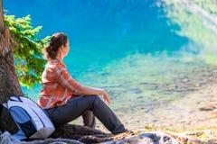 Μια γυναίκα κάθεται από τη λίμνη του ματιού θάλασσας στα βουνά α Tatra Στοκ Εικόνα
