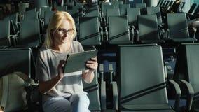 Μια γυναίκα κάθεται μόνο μεταξύ των σειρών των κενών καρεκλών στη αίθουσα αναμονής Χρησιμοποιεί μια ταμπλέτα φιλμ μικρού μήκους