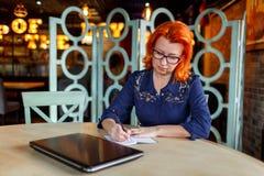 Μια γυναίκα κάθεται σε έναν πίνακα σε έναν καφέ και κάνει τις σημειώσεις σε ένα σημειωματάριο Στοκ Εικόνες