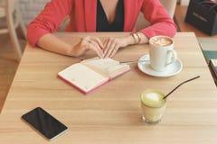 Μια γυναίκα κάθεται σε έναν πίνακα σε έναν καφέ με ένα εφεδρικό βιβλίο Στις επιτραπέζιες στάσεις μια κούπα του cappuccino, ενός τ στοκ φωτογραφία με δικαίωμα ελεύθερης χρήσης