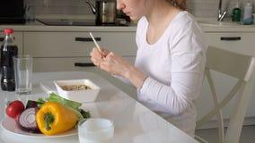 Μια γυναίκα κάθεται σε έναν πίνακα τρώγοντας τα κινεζικά νουντλς και τα φρέσκα λαχανικά απόθεμα βίντεο