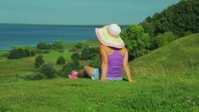 Μια γυναίκα κάθεται σε ένα βουνό και θαυμάζει την άποψη της λίμνης Πυροβολισμός από την πλάτη φιλμ μικρού μήκους