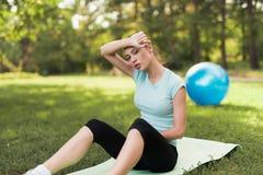Μια γυναίκα κάθεται σε μια κουβέρτα για τη γιόγκα και στηρίζεται μετά από ένα workout Πίσω από την είναι μια μπλε σφαίρα για τη γ Στοκ Φωτογραφίες