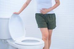 Μια γυναίκα κάθεται στην τουαλέτα με τη διάρροια ή το δυσκοίλιο πόνο γ στοκ φωτογραφία με δικαίωμα ελεύθερης χρήσης