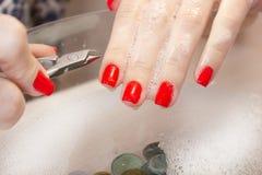 Μια γυναίκα κάνει ένα μανικιούρ με ένα εργαλείο Κόκκινα καρφιά που ενυδατώνονται σε ένα λουτρό με το νερό Στοκ Εικόνα