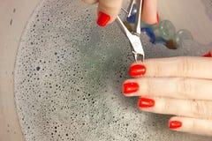 Μια γυναίκα κάνει ένα μανικιούρ με ένα εργαλείο Κόκκινα καρφιά που ενυδατώνονται σε ένα λουτρό με το νερό Στοκ Φωτογραφία