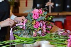 Μια γυναίκα κάνει μια ανθοδέσμη των λουλουδιών στον πίνακα ρόδινα τριαντάφυλλα Μια γυναίκα που επιδένει το α Στοκ Εικόνες