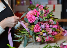 Μια γυναίκα κάνει μια ανθοδέσμη των λουλουδιών στον πίνακα ρόδινα τριαντάφυλλα Μια γυναίκα που επιδένει το α Στοκ Φωτογραφία