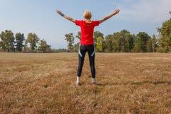 Μια γυναίκα κάνει τη γυμναστική σε ένα πάρκο Στοκ εικόνα με δικαίωμα ελεύθερης χρήσης