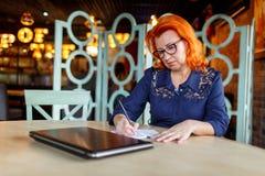 Μια γυναίκα κάνει τις σημειώσεις σε ένα σημειωματάριο σε ένα γραφείο δίπλα σε ένα κλειστό lap-top Στοκ Εικόνα