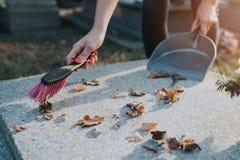 Μια γυναίκα καθαρίζει τον τάφο Στοκ φωτογραφία με δικαίωμα ελεύθερης χρήσης