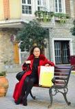 Μια γυναίκα καθόταν σε έναν στο κέντρο της πόλης πάγκο Στοκ Εικόνες