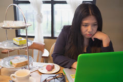 Μια γυναίκα και ένας υπολογιστής με το πρόσωπο σκέψης στο χρόνο τσαγιού Στοκ εικόνα με δικαίωμα ελεύθερης χρήσης