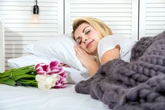 Μια γυναίκα κοιμάται, στις ανθοδέσμες κρεβατιών τουλιπών της ρομαντική έκπληξη Ημέρα γυναικών ` s μητέρα s ημέρας στοκ εικόνες