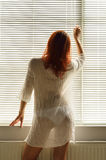 Μια γυναίκα κοντά στο παράθυρο στο σπίτι στοκ εικόνες