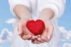 Μια γυναίκα κρατά μια καρδιά στους φοίνικές της στοκ εικόνες