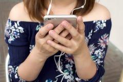 Μια γυναίκα κρατά μια κινητή συσκευή Στοκ Εικόνες