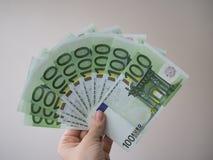 Μια γυναίκα κρατά στο χέρι της πολλά τραπεζογραμμάτια στις μετονομασίες του ανεμιστήρα 100 ευρώ στοκ εικόνα με δικαίωμα ελεύθερης χρήσης