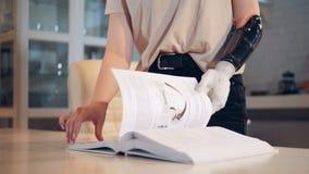 Μια γυναίκα κτυπά τις σελίδες ενός βιβλίου με το ρομποτικό χέρι, κλείν απόθεμα βίντεο
