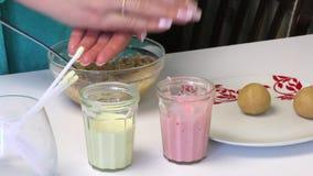 Μια γυναίκα κυλά τις σφαίρες μπισκότων γιατί το κέικ σκάει Κοντά στον πίνακα είναι γυαλιά με την τήξη, τα ραβδιά και τις έτοιμες  απόθεμα βίντεο