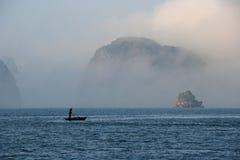 Μια γυναίκα κωπηλατεί στον κόλπο Halong (Βιετνάμ) Στοκ Εικόνες