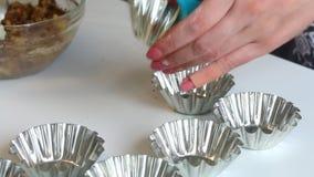Μια γυναίκα λαδώνει με τις μορφές μετάλλων ηλιέλαιων για τα κέικ ψησίματος Χρησιμοποιεί μια ειδική βούρτσα φιλμ μικρού μήκους