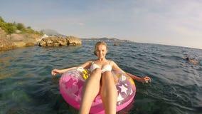 Μια γυναίκα λούζει στη θάλασσα με έναν ρόδινο κύκλο απόθεμα βίντεο