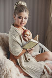 Μια γυναίκα με ένα βιβλίο και ένα ώριμο μήλο σε ένα χέρι Στοκ Εικόνα