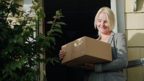 Μια γυναίκα με ένα δέμα στέκεται στο κατώφλι του σπιτιού της Εξετάζει τη κάμερα, χαμόγελο Παράδοση των δεμάτων απόθεμα βίντεο
