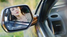 Μια γυναίκα με ένα κλάμα κάθεται στο αυτοκίνητο Στον οπισθοσκόπο καθρέφτη διορθώνει τη σύνθεση, όλες κλαμένες Έννοια - απόθεμα βίντεο