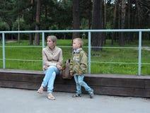 Μια γυναίκα με ένα μικρό παιδί αγοριών που περπατά στη συνεδρίαση πάρκων σε μια στήριξη πάγκων στοκ εικόνα