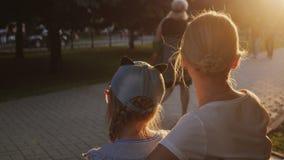 Μια γυναίκα με ένα παιδί κάθεται εδώ κοντά σε έναν πάγκο στο πάρκο, οι περαστικοί περπατούν κοντά απόθεμα βίντεο