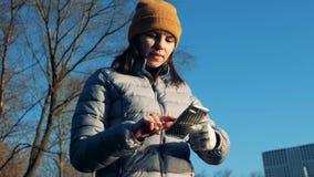 Μια γυναίκα με ένα συνθετικό χέρι κοιτάζει βιαστικά το κινητό τηλέφωνό της υπαίθρια απόθεμα βίντεο