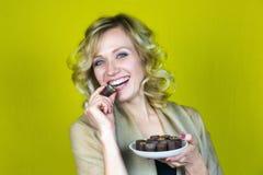 Μια γυναίκα με ένα όμορφο χαμόγελο τρώει την καραμέλα στοκ φωτογραφία με δικαίωμα ελεύθερης χρήσης
