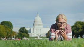 Μια γυναίκα με ένα smartphone βρίσκεται σε έναν χορτοτάπητα στα πλαίσια του Capitol στην Ουάσιγκτον Μελέτη και ταξίδι απόθεμα βίντεο