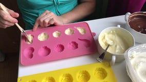 Μια γυναίκα με μια βούρτσα λαδώνει τη μορφή σιλικόνης με τη λειωμένη άσπρη σοκολάτα Μαγειρεύοντας επιδόρπιο απόθεμα βίντεο
