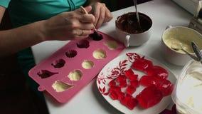 Μια γυναίκα με μια βούρτσα λαδώνει τη μορφή σιλικόνης με τη λειωμένη σκοτεινή σοκολάτα Μαγειρεύοντας επιδόρπιο απόθεμα βίντεο