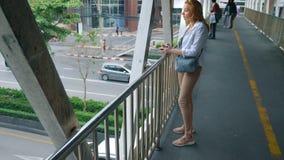 Μια γυναίκα με μια κάμερα περπατά μέσω των οδών μιας μεγάλης σύγχρονης πόλης στοκ εικόνα με δικαίωμα ελεύθερης χρήσης
