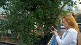 Μια γυναίκα με μια κάμερα περπατά μέσω των οδών μιας μεγάλης σύγχρονης πόλης στοκ φωτογραφίες