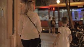 Μια γυναίκα με μια μεταφορά μωρών και με έναν παλαιότερο γιο που περπατά κάτω από την οδό βραδιού φιλμ μικρού μήκους