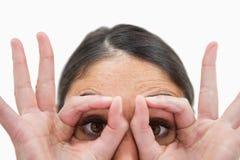 Μια γυναίκα με τα δάχτυλά της γύρω από τα μάτια της Στοκ εικόνα με δικαίωμα ελεύθερης χρήσης