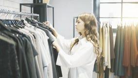 Μια γυναίκα με την καφετιά τρίχα επιλέγει τα ενδύματα για να αγοράσει μέσα ένα κατάστημα Στοκ Εικόνες