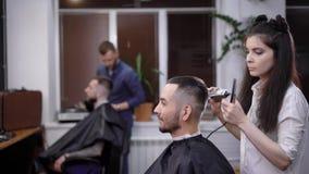 Μια γυναίκα με τη μακριά σκοτεινή τρίχα που αποδεικνύεται κομμωτής, κόβει την τρίχα ενός πελάτη του barbershop, ένας άνδρας θέλει απόθεμα βίντεο