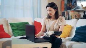 Μια γυναίκα με τους προσθετικούς τύπους χεριών σε ένα lap-top, κλείνει επάνω απόθεμα βίντεο