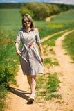 Μια γυναίκα με το λουλούδι παπαρουνών στη μέση περπατά μόνο στο δρόμο κάρρων στοκ εικόνα