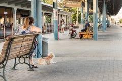 Μια γυναίκα με το σκυλί της που περιμένει το τραίνο στην πλατφόρμα του θορίου στοκ φωτογραφία