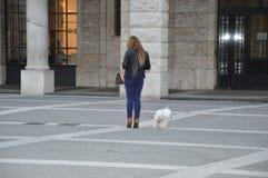 Μια γυναίκα με το σκυλί της σε ένα κενό τετράγωνο στην Ιταλία και φροντίζει το smartphone της στοκ φωτογραφίες