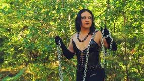 Μια γυναίκα μιας μάγισσας στα μαύρα ενδύματα με μια αλυσίδα σε την παραδίδει το δάσος μια φωτεινή ημέρα αποκριές Ύφος Gothick απόθεμα βίντεο