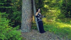 Μια γυναίκα μιας μάγισσας στα μαύρα ενδύματα σε ένα δάσος είναι δεμένη με τις αλυσίδες σε ένα δέντρο αποκριές Ύφος Gothick απόθεμα βίντεο